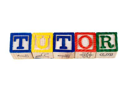 The word tutor, spelled using wooden letter blocks, isolated against a white background